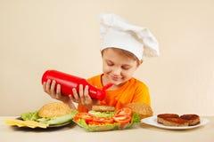 El pequeño muchacho sonriente en sombrero de los cocineros pone la salsa en la hamburguesa Imágenes de archivo libres de regalías
