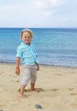 El pequeño muchacho sonriente lindo juega en la playa Imagenes de archivo