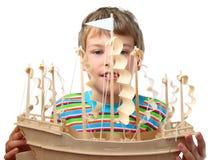 El pequeño muchacho sostiene la nave de madera artificial Imagen de archivo