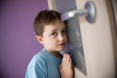 El pequeño muchacho triste oye por casualidad la lucha de sus padres - B&W imagen de archivo