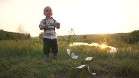 El pequeño niño alegre sostiene el billete de banco del dinero y lo lanza en la tierra, cámara lenta almacen de video