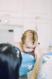El pequeño niño aprende ayudar a padres a guardar su cabeza Fotos de archivo