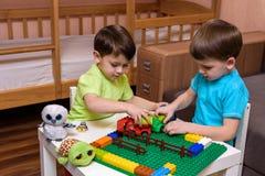 El pequeño niño caucásico que juega con las porciones de plástico colorido bloquea interior Embrome la camisa que lleva del mucha Foto de archivo