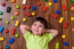 El pequeño niño caucásico que juega con las porciones de plástico colorido bloquea interior Embrome la camisa que lleva del mucha Fotografía de archivo libre de regalías