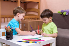 El pequeño niño caucásico que juega con las porciones de plástico colorido bloquea interior Embrome la camisa que lleva del mucha Imagen de archivo libre de regalías