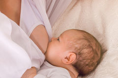 El pequeño niño chupa su pecho de la madre fotografía de archivo libre de regalías