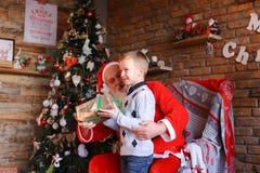 El pequeño niño corre a Santa Claus, se sienta en rodillas y hace deseo, Foto de archivo