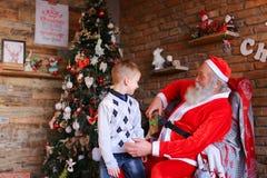 El pequeño niño corre a Santa Claus, se sienta en rodillas y hace deseo, Foto de archivo libre de regalías