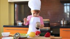 El pequeño niño del retrato en traje del cocinero ayuda a su madre a cocinar en la cocina almacen de video