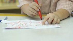 El pequeño niño desconocido pinta imágenes con el rotulador almacen de video