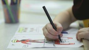 El pequeño niño desconocido pinta imágenes con el rotulador almacen de metraje de vídeo