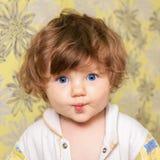 El pequeño niño divertido dobló los labios del arco y la mirada de la cámara Foto de archivo libre de regalías