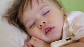 El pequeño niño duerme en sala de hospital en la temperatura blanca del lecho y de las medidas con el termómetro Tratamiento de n almacen de metraje de vídeo