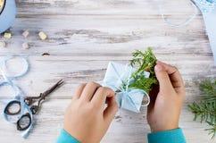 El pequeño niño embala y adorna un regalo hecho a mano de la Navidad Foto de archivo
