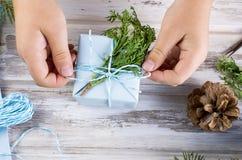 El pequeño niño embala y adorna un regalo hecho a mano de la Navidad Fotos de archivo libres de regalías