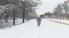 El pequeño niño en bosque del invierno corre a través de nieve hacia cámara metrajes