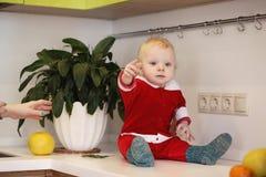 El pequeño niño en la cocina se sienta en una tabla foto de archivo