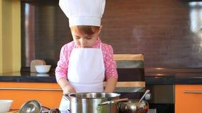 El pequeño niño encantador en traje del cocinero asperja la comida del azúcar en la cocina metrajes
