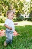 El pequeño niño está en la hierba Imágenes de archivo libres de regalías