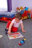 El pequeño niño está jugando con rompecabezas colorido Fotos de archivo libres de regalías