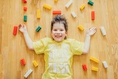 El pequeño niño está poniendo con el plástico colorido Foto de archivo