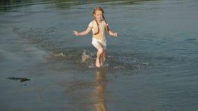 El pequeño niño feliz lindo que juega y que salpica en el mar agita, muchacha sana que corre la cámara lenta estupenda metrajes