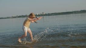 El pequeño niño feliz lindo que juega y que salpica en el mar agita, muchacha sana que corre la cámara lenta estupenda almacen de metraje de vídeo