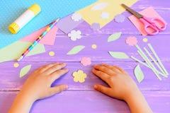 El pequeño niño hace una tarjeta de felicitación para la madre El papel coloreado, las plantillas, las flores y las hojas cortaro Fotos de archivo libres de regalías