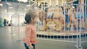 El pequeño niño hermoso de la muchacha, colocándose cerca del carrusel, llevando a cabo las manos por la cerca, sorprendió ojos almacen de metraje de vídeo