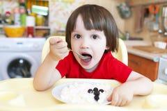 El pequeño niño lindo come el quark y la baya con apetito fotografía de archivo