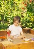 El pequeño niño lindo está jugando en la salvadera en el patio Foto de archivo libre de regalías