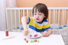 El pequeño niño lindo hizo las piruletas de playdough y de palillos Foto de archivo