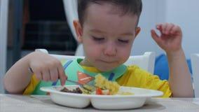 El pequeño niño lindo se está sentando en una tabla en un babero y come su propio puré, el bebé come dispuesto Concepto Childhool metrajes