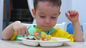 El pequeño niño lindo se está sentando en una tabla en un babero y come su propio puré, el bebé come dispuesto Pequeña consumició almacen de video