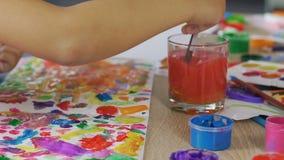 El pequeño niño mezcla todos los colores posibles en un trozo de papel, mente imaginativa metrajes