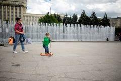 El pequeño niño monta un monopatín en parque Imagenes de archivo