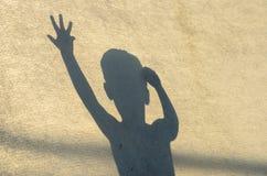 El pequeño niño muestra el teatro de la sombra Fotografía de archivo