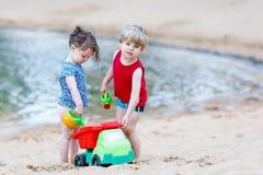 El pequeño niño pequeño y la muchacha que juegan así como la arena juega Imagen de archivo libre de regalías