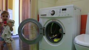 El pequeño niño pone el lavadero en la lavadora almacen de metraje de vídeo