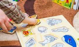 El pequeño niño pone el rompecabezas simple en el piso Imagen de archivo libre de regalías