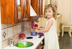 El pequeño niño preescolar activo de la edad, niña pequeña linda con el pelo rizado rubio, muestra jugar la cocina, hecha de la m Foto de archivo libre de regalías