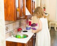 El pequeño niño preescolar activo de la edad, niña pequeña linda con el pelo rizado rubio, muestra jugar la cocina, hecha de la m Imagen de archivo