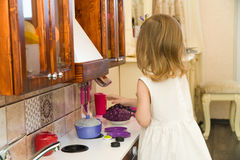 El pequeño niño preescolar activo de la edad, niña pequeña linda con el pelo rizado rubio, muestra jugar la cocina, hecha de la m Fotos de archivo libres de regalías