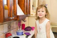 El pequeño niño preescolar activo de la edad, niña pequeña linda con el pelo rizado rubio, muestra jugar la cocina, hecha de la m Imágenes de archivo libres de regalías
