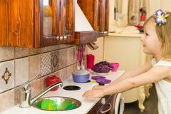 El pequeño niño preescolar activo de la edad, niña pequeña linda con el pelo rizado rubio, muestra jugar la cocina, hecha de la m Foto de archivo