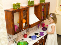 El pequeño niño preescolar activo de la edad, niña pequeña linda con el pelo rizado rubio, muestra jugar la cocina, hecha de la m Imagen de archivo libre de regalías
