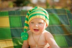 El pequeño niño se sienta en el sombrero Fotografía de archivo