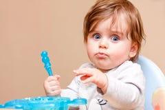 El pequeño niño se sienta en una tabla y come Imagen de archivo libre de regalías