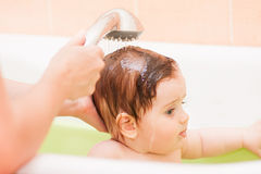 El pequeño niño vierte fuera de la ducha en el cuarto de baño Foto de archivo libre de regalías