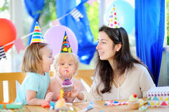 El pequeño niño y su madre celebran la fiesta de cumpleaños con la decoración y las tortas coloridas Imagenes de archivo